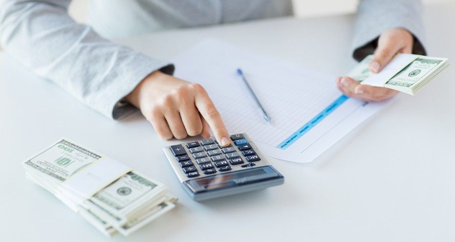 usiness, finance, tax and people concept - close up of woman hands counting us dollar money with calculator